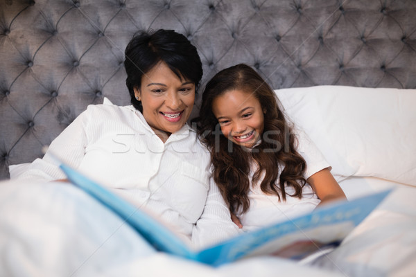 Happy grandmother and granddaughter reading book on bed Stock photo © wavebreak_media