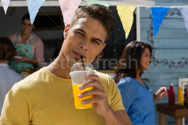 Young man having juice while standing by food truck Stock photo © wavebreak_media