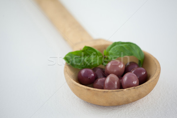 Close up of brown olives with herb in wooden ladle Stock photo © wavebreak_media