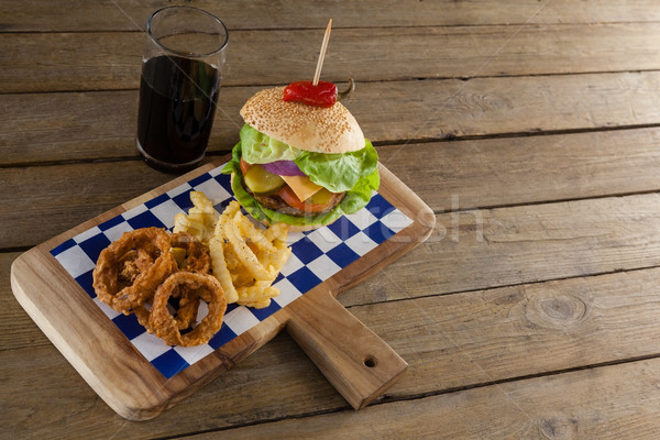 Hamburger, onion ring and french fries with cold drink on chopping board Stock photo © wavebreak_media