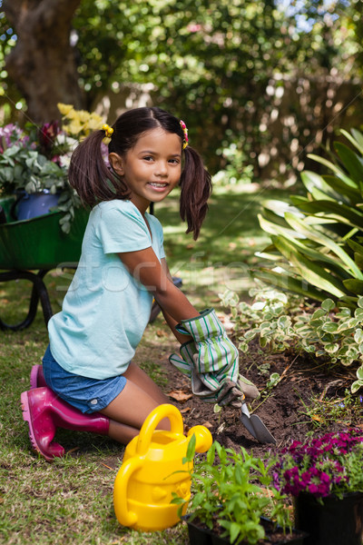 Portré mosolyog lány térdel föld virág Stock fotó © wavebreak_media