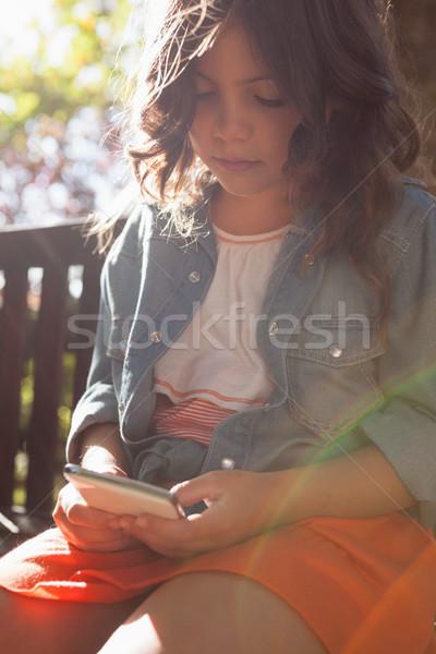 Dziewczyna telefonu komórkowego posiedzenia ławce drewna Zdjęcia stock © wavebreak_media