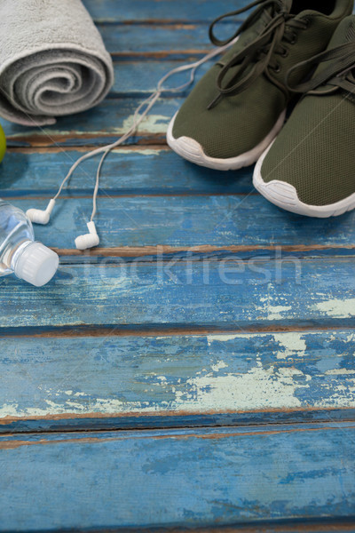 High angle view of sports shoes and napkin by headphones with bottle on table Stock photo © wavebreak_media
