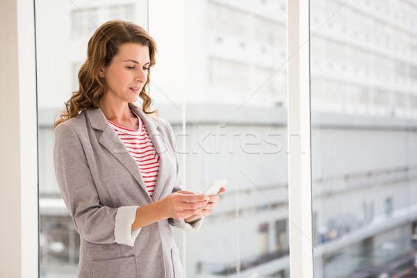 Casual businesswoman using smartphone Stock photo © wavebreak_media