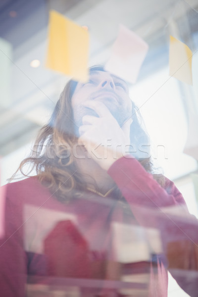 Low angle view of thoughtful businessman looking at sticky note Stock photo © wavebreak_media
