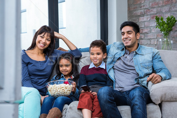 Happy young family eating popcorn while watching tv Stock photo © wavebreak_media
