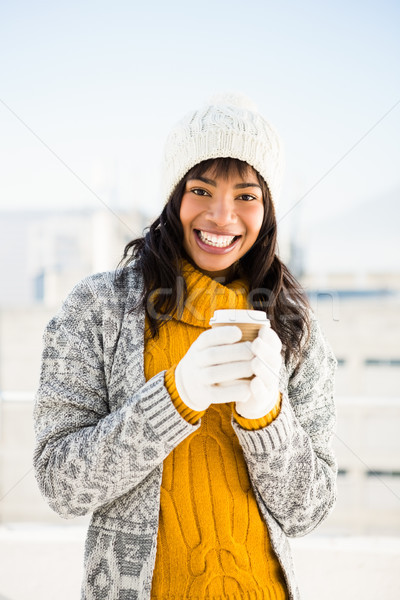 Smiling woman wearing winter clothes and holding coffee Stock photo © wavebreak_media