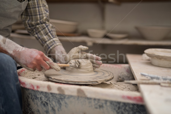 Mid section of male potter molding plate with hand tool Stock photo © wavebreak_media
