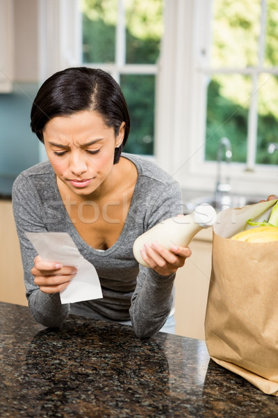 Frowning brunette holding receipt and milk Stock photo © wavebreak_media
