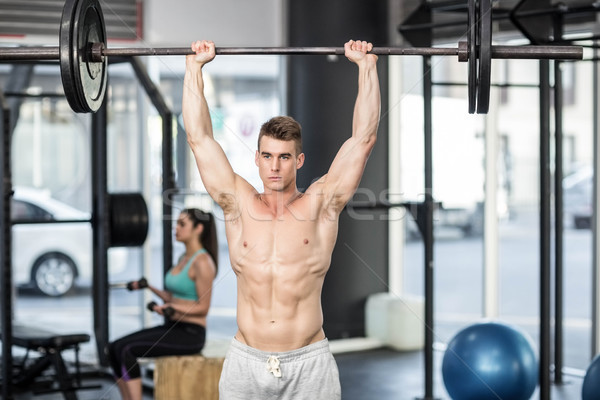 Stock photo: Fit couple lifting dumbbells