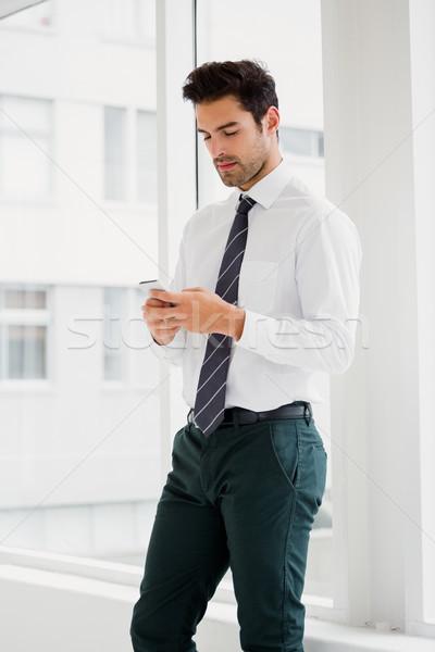 Férfi tart okostelefon sms chat munka iroda Stock fotó © wavebreak_media