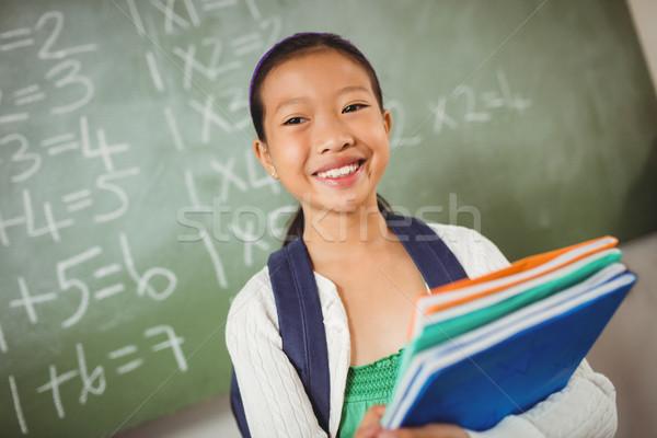 Studentessa guardando fotocamera sorridere libri bambino Foto d'archivio © wavebreak_media