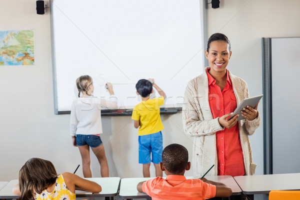 Smiling teacher using a tablet while pupils are working Stock photo © wavebreak_media