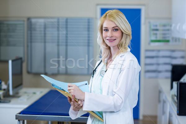 Portrait of woman vet writing something on document Stock photo © wavebreak_media
