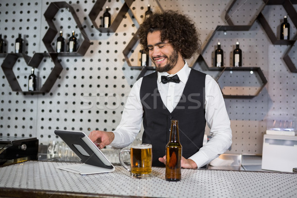 Bartender using digital tablet at bar counter Stock photo © wavebreak_media
