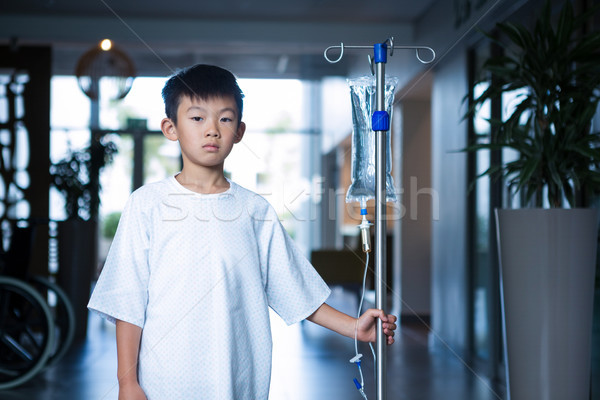 Boy patient holding intravenous iv drip stand in corridor Stock photo © wavebreak_media