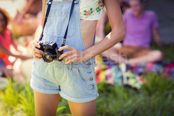 Woman holding camera at campsite Stock photo © wavebreak_media