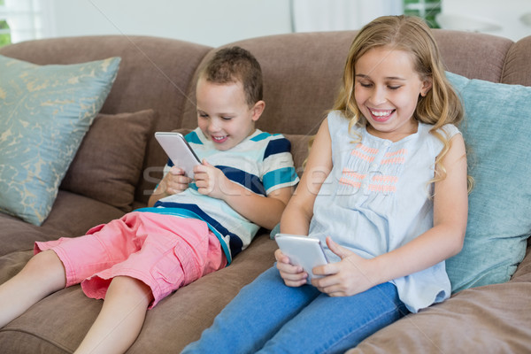 Smiling sister and brother sitting on couch using mobile phone in living room Stock photo © wavebreak_media