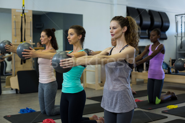 Fit women performing stretching exercise with fitness ball in gym Stock photo © wavebreak_media