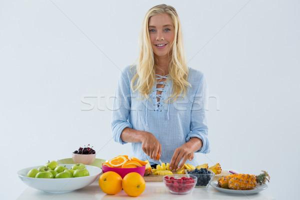Portrait of woman cutting fruits on chopping board Stock photo © wavebreak_media