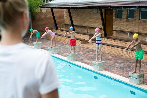 Female trainer looking at children at poolside Stock photo © wavebreak_media