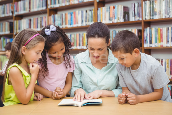 Pupils and teacher reading book in library Stock photo © wavebreak_media