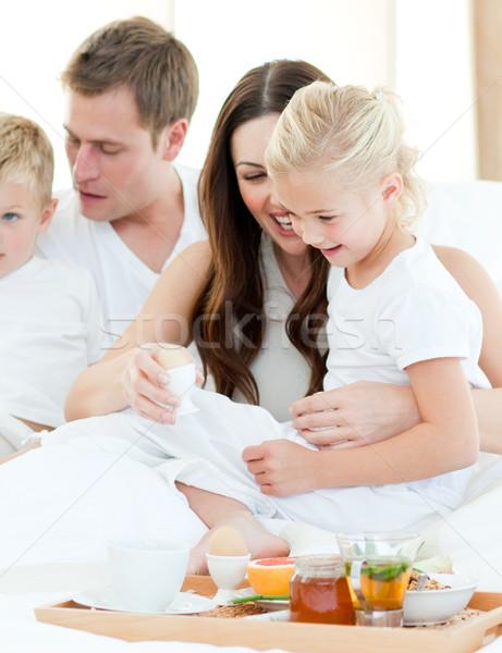 Elated family having breakfast sitting on bed Stock photo © wavebreak_media