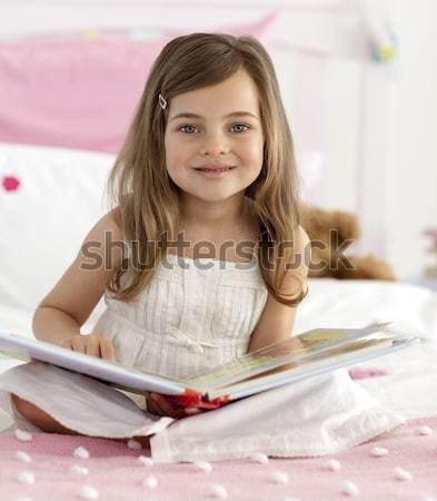 Beautiful little girl reading in bed Stock photo © wavebreak_media
