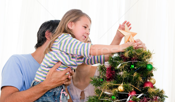Little girl placing a star in a Christmas tree with her parents Stock photo © wavebreak_media