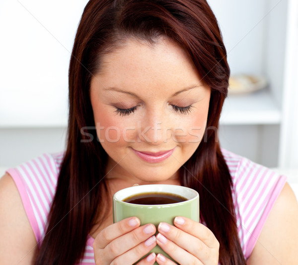 Delighted woman holding a cup of coffee at home in the living-room Stock photo © wavebreak_media