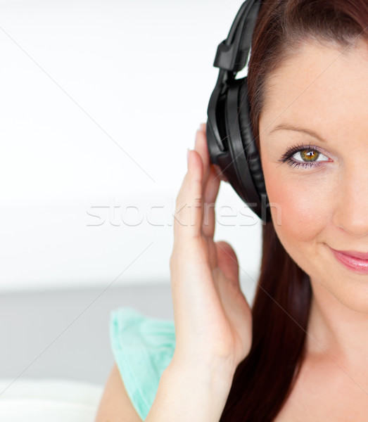 Pleased woman listening to music with headphones at home in the living-room Stock photo © wavebreak_media