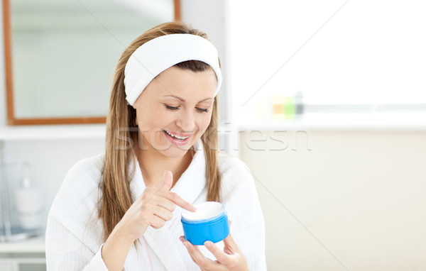 Radiant woman putting cream on her face wearing a headband in the bathroom at home Stock photo © wavebreak_media