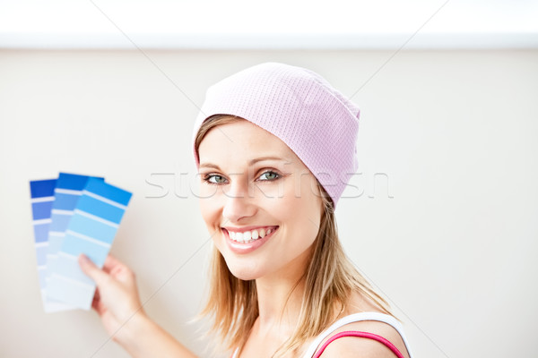 Joyful young woman choosing color for painting a room in her new house Stock photo © wavebreak_media