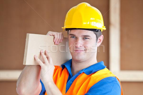 Fiatal férfi munkás hordoz fa deszka munka Stock fotó © wavebreak_media
