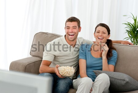 Happy man watching television with his girlfriend sitting on the sofa at home Stock photo © wavebreak_media
