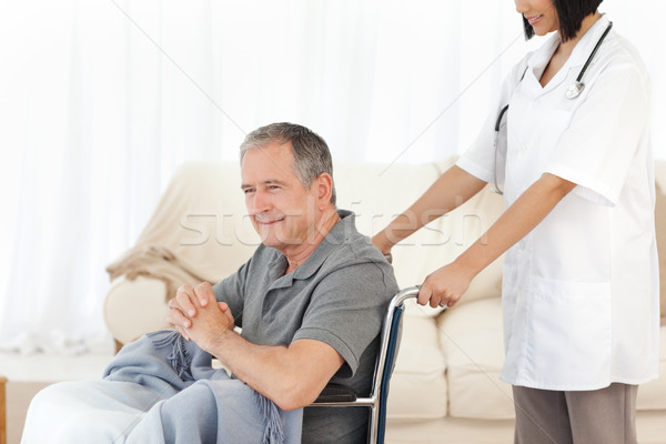 Man in his wheelchair with his nurse at home Stock photo © wavebreak_media