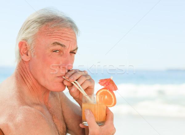 Gepensioneerd man drinken cocktail strand water Stockfoto © wavebreak_media