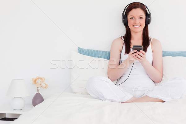 Prachtig vrouw luisteren naar muziek hoofdtelefoon vergadering bed Stockfoto © wavebreak_media
