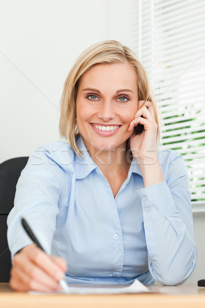 Portrait of a businesswoman looking into camera while noting something in her office Stock photo © wavebreak_media