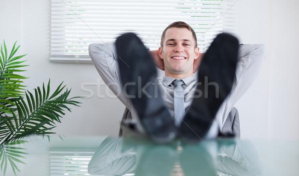 Smiling businessman sitting back behind a table Stock photo © wavebreak_media