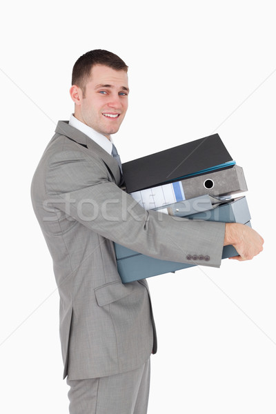 Stock photo: Portrait of a young businessman holding a stack of binders against a white background
