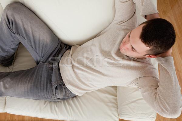 Jeune homme canapé salon maison design meubles Photo stock © wavebreak_media