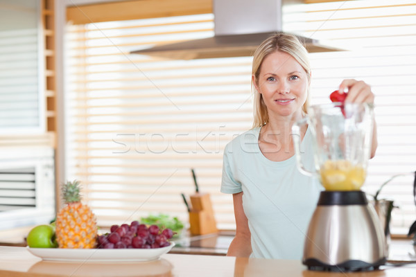 Smiling woman dropping strawberry into the blender Stock photo © wavebreak_media