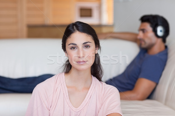 Woman posing while her boyfriend is listening to music in their living room Stock photo © wavebreak_media