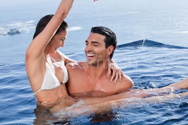 Férfi tart játékos barátnő úszómedence víz Stock fotó © wavebreak_media