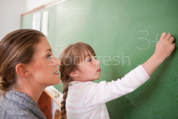 Teacher and a pupil making an addition on a blackboard Stock photo © wavebreak_media