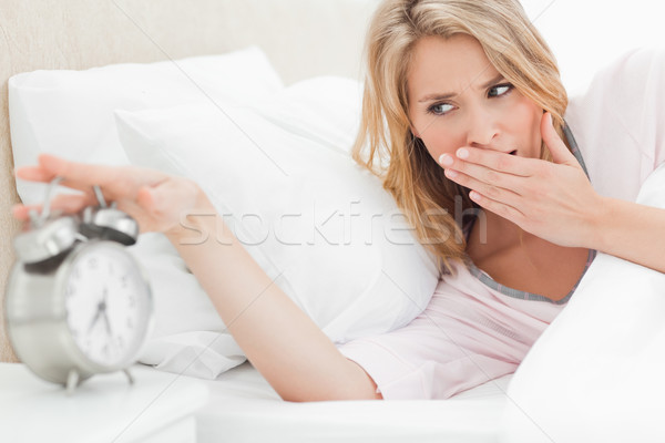 A woman in bed is leaning up and reaching to turn off the alarm as she yawns and checks the time Stock photo © wavebreak_media