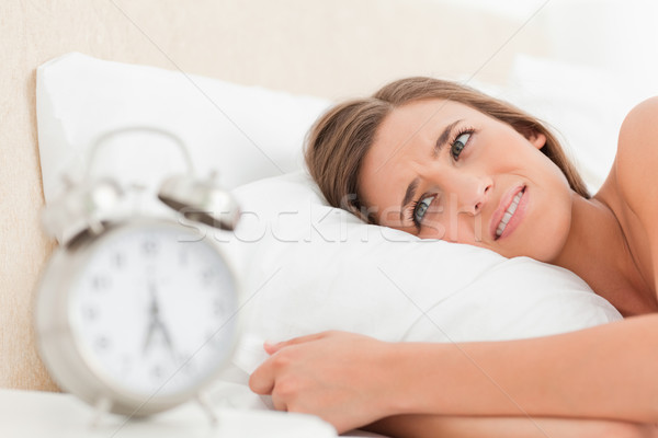 A woman in bed awake and slightly annoyed by her alarm clock. Stock photo © wavebreak_media