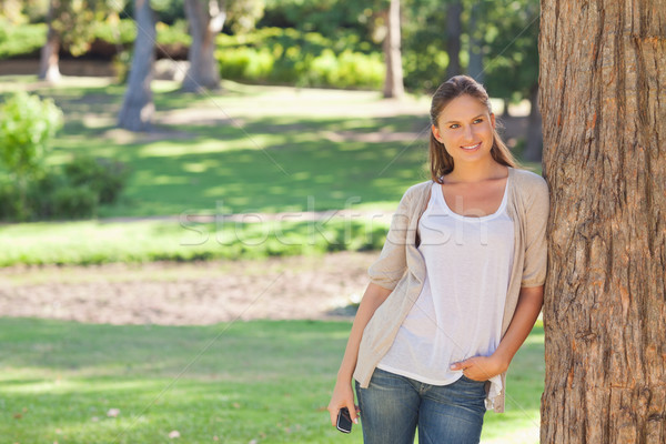 Woman with a cellphone leaning against a tree Stock photo © wavebreak_media