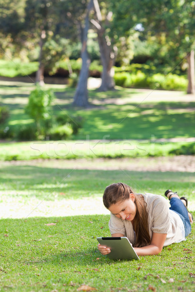 Woman laying on the lawn using a tablet computer Stock photo © wavebreak_media